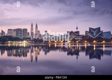 Moody lever du soleil à Kuala Lumpur en Malaisie. Reflet de l'horizon urbain dans le lac. Banque D'Images