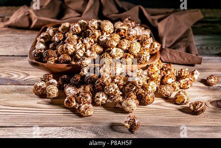 Maïs soufflé au caramel dans un bol en bois sur un fond de bois. Clé faible éclairage. Focus sélectif. Close-up Banque D'Images