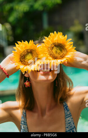 Beautiful smiling girl in bikini holding sunflowers à sunny day Banque D'Images
