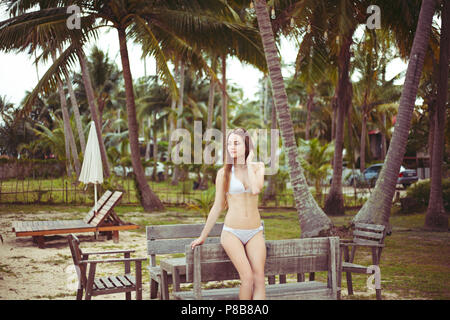 Attractive Woman in bikini leaning on banc en bois sur la plage Banque D'Images