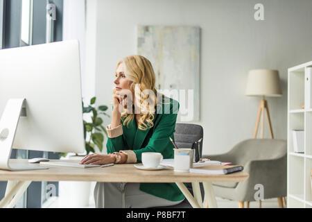 Pensive businesswoman looking away lors de l'utilisation d'ordinateur de bureau au travail Banque D'Images