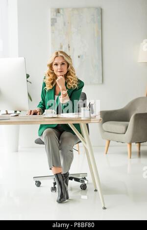 Femme d'âge moyen à l'aide de l'ordinateur de bureau et à la caméra au lieu de travail à Banque D'Images