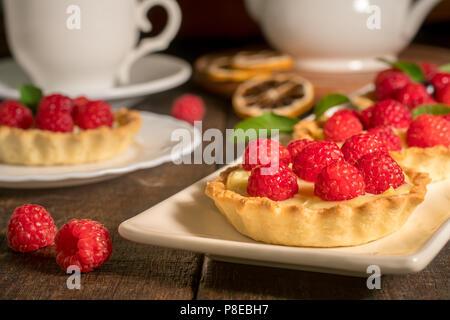 Gâteaux aux framboises sur la table. Une tasse de thé avec des gâteaux. Dessert sucré. Produit culinaire avec des baies. Banque D'Images