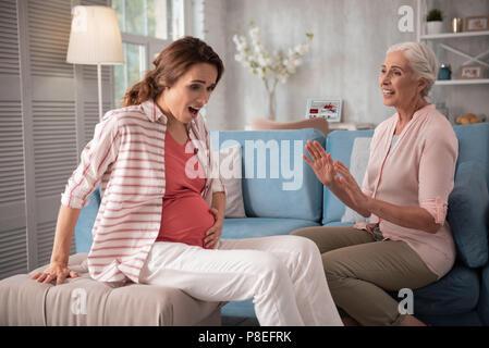 Dark-haired femme enceinte sentiment sentiment étonné se déplace de petit bébé Banque D'Images