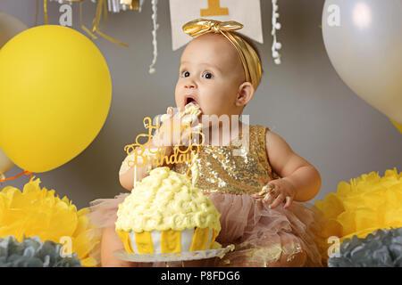 Bébé garçon curieux doigt piquer dans son premier gâteau d'anniversaire Banque D'Images
