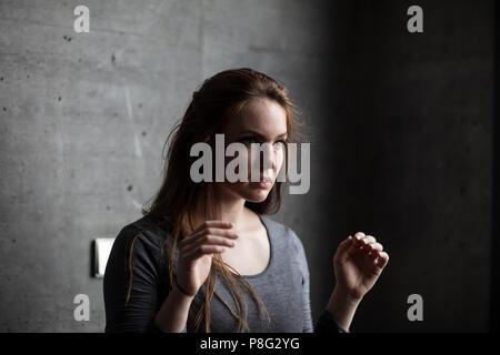 Young woman raising her arms debout derrière un mur de béton gris. L'angle de vue. Plan moyen. Banque D'Images