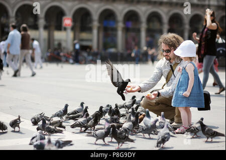 Adorable petite fille et son père se nourrir les pigeons à l'extérieur