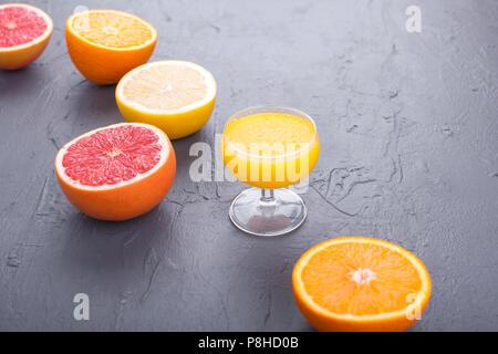 Les agrumes avec un assortiment de tranches et jus dans un verre. Arrière-plan de pierre grise. Les vitamines et la santé dans l'alimentation. Copy space