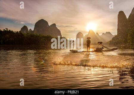 Le Cormorant Fisherman casting net sur la rivière Li, Xingping, Guilin Chine, comme le soleil se couche derrière les montagnes karstiques derrière lui. Banque D'Images