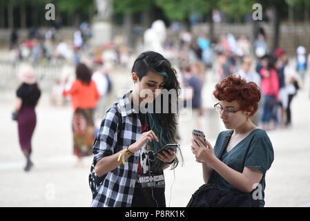 Juillet 14, 2016 - Paris, France: Français arts Calypso (L), 17 yo, et Lorenz, 18yo, participer à une chasse en masse Pokemon le Jardin du Luxembourg, dans le centre de Paris. Des centaines de joueurs du nouveau Pokemon le jeu de Go a montré jusqu'à prendre part à une chasse massive en dépit de la tentative des autorités d'annuler l'événement. En dépit de jouer en solo pour la plupart, les Pokemon Rendez-vous apprécié des utilisateurs d'interagir et de rencontrer d'autres joueurs. Des millions d'utilisateurs ont déjà téléchargé le jeu, ce qui oblige les utilisateurs à prendre sur-écran personnages Pokémon à l'aide de leur emplacement. *** FRANCE / PAS DE VENTES À FR Banque D'Images