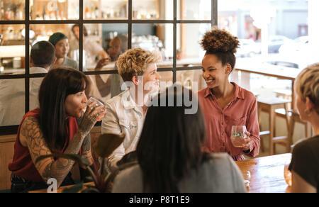 Young female friends rire ensemble autour d'un verre dans un bistro Banque D'Images