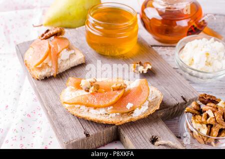 Petit déjeuner avec des sandwichs. plateau de fromage ricotta et poires confiture. Tasse de thé et théière en verre. Vue de dessus, copy space Banque D'Images