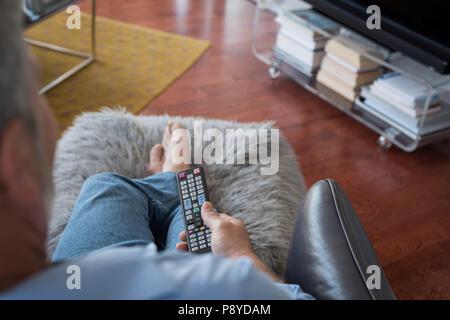 Changer les voies de l'homme en regardant la télévision dans la salle de séjour Banque D'Images