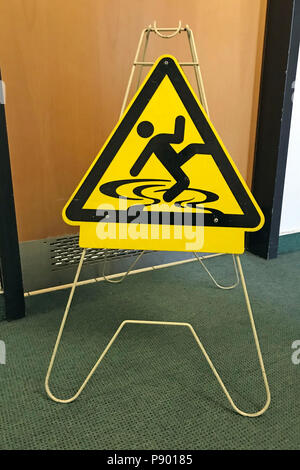 Berlin, Allemagne, la signalisation danger de glisser en face d'une porte des toilettes Banque D'Images