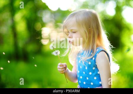 Jolie petite blonde girl blowing off un pissenlit sur belle journée ensoleillée Banque D'Images