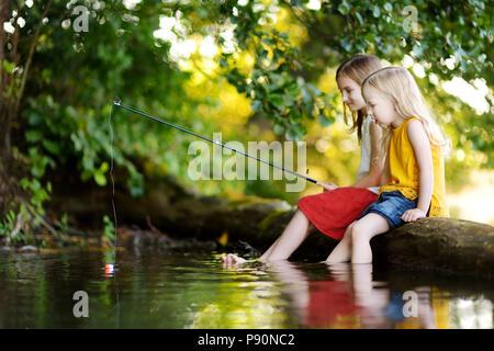 Deux mignonnes petites filles s'amuser par une rivière à belle soirée d'été. Soeurs pêchait à l'aide d'une canne à pêche sur la journée chaude et ensoleillée. Banque D'Images