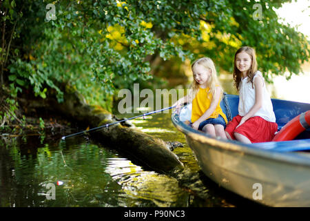 Deux mignonnes petites filles s'amusant dans un bateau par une rivière à belle soirée d'été. Soeurs pêchait à l'aide d'une canne à pêche sur la journée chaude et ensoleillée. Banque D'Images