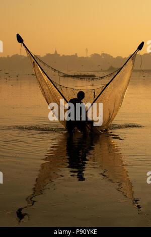 Silhouette de Myanmar pêcheur en action attraper les poissons d'eau douce dans la rivière de la nature, les pêcheurs traditionnels au coucher du soleil près du lac Inle, Myanmar Banque D'Images