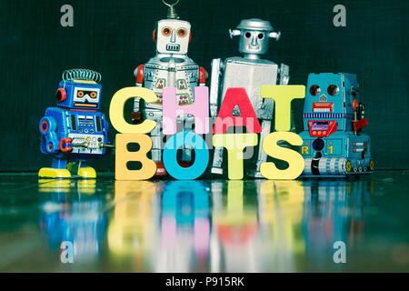 Le mot CHAT BOTS avec rtro robots sur un sol en bois avec réflexion Banque D'Images