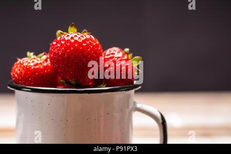 Petits fruits frais mûrs. Des fraises dans la tasse sur la table en bois Banque D'Images