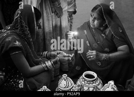Les femmes du Rajasthan placer une bougie dans un pot en argile dans le cadre du festival à JOHDPUR GANGUR - RAJASTHAN, INDE Banque D'Images