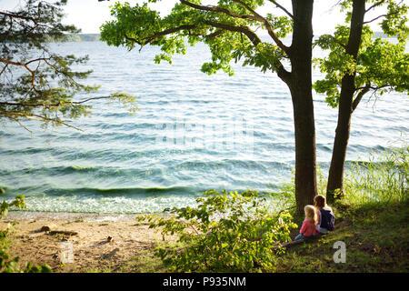 Deux mignonnes petites soeurs assis au bord du lac avec sa vue sur le coucher de soleil. Les enfants d'explorer la nature. Activités en famille l'été. Banque D'Images