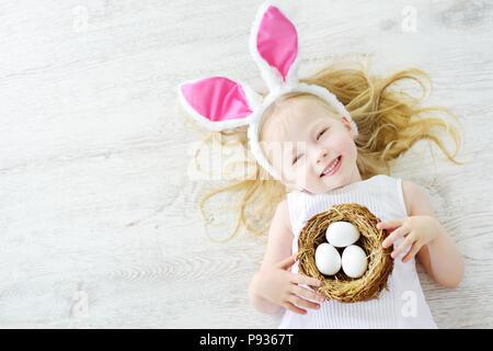 Cute little girl wearing Bunny Ears jouant sur la chasse aux œufs de Pâques. Adorable enfant célébrer Pâques à la maison. Banque D'Images