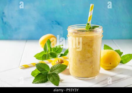 Apricot smoothie milkshake ou sur un fond de bois blanc. Régime alimentaire sain juteux vitamine boire ou vegan food concept. Banque D'Images