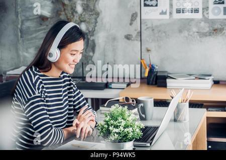 Young Asian businesswoman décontractée sur le bras de bureau reste posent avec ordinateur portable et l'écoute de la musique via la prise casque et penser à travailler ,travailler à domicile avec Banque D'Images