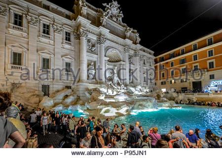 Fontaine de Trevi à Rome Italie colorée et éclairée le soir avec les touristes qui l'entoure sur une chaude soirée d'été. Banque D'Images