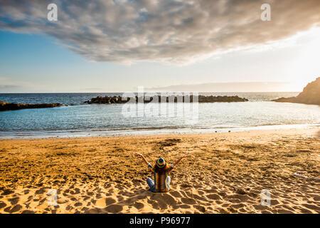 Concept de bonheur avec jeune femme assise sur la plage et s'étreindre l'océan et la nature en face d'elle. la liberté et l'indépendance de