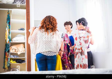 Groupe de trois jeunes femmes de race blanche à la maison en choisissant la robe prêt pour la nuit événements et célébrer ensemble dans l'amitié. smiles et nice leisu Banque D'Images