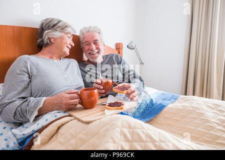 Beau portrait de senior couple enjoying et rire ensemble se réveiller tôt le matin. grillé et de marmelade et de café. Solidarité et fo Banque D'Images