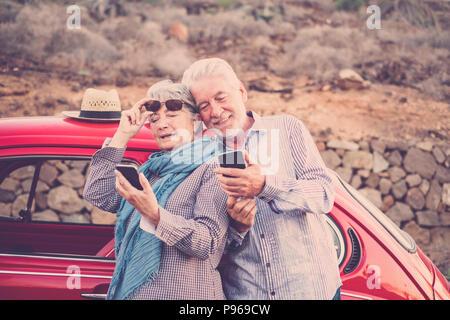 Senior adult couple vérifier et regarder le téléphone mobile pour se connecter à Internet ou prendre une photo. selfies vintage voiture rouge prêt à voyager et partout en e