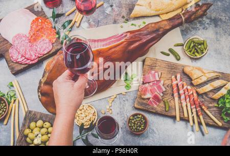 Mans hand holding wine glass frome tableau ci-dessus avec spanit ou hors-d'italien, toute la jambe de jambon serrano et un rouge vin rose Banque D'Images