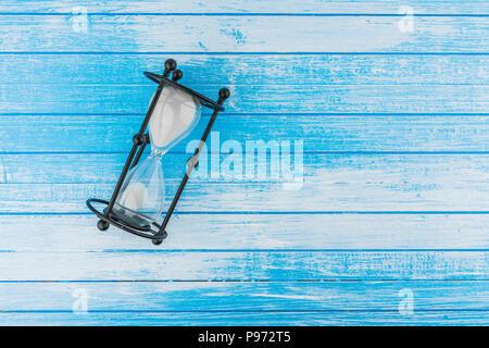 Sablier ancien sur bois peint bleu et blanc à haut contraste de fond Vue de dessus Banque D'Images