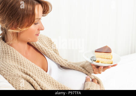 Beautiful happy pregnant woman eating cake in bed Banque D'Images