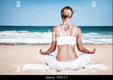 Femme méditant sur la plage, vue arrière d'une saine slim girl sitting in lotus pose et bénéficiant d'une belle vue sur la mer, la pleine conscience Banque D'Images