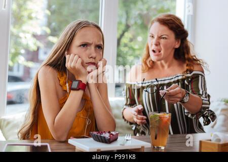 Blue-eyed lycéenne en colère se disputer avec mère Banque D'Images