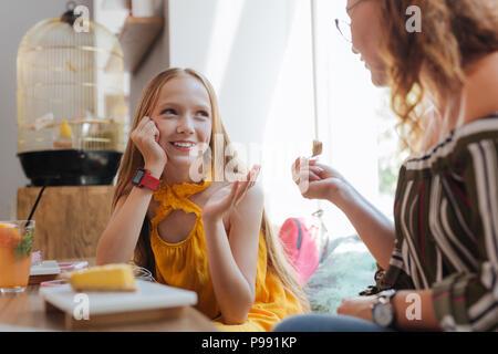 Transmission d'adolescent aux cheveux blonds et profiter de parler à sa mère Banque D'Images