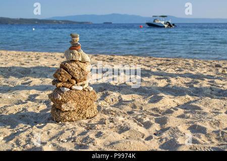 L'équilibre des pierres sur la plage tourné au coucher du soleil. Banque D'Images
