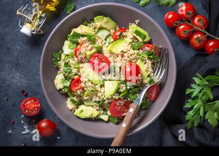 La nourriture végétalienne. Salade de quinoa aux épinards, d'avocat et les tomates de pierre sombre tableau. Close up. Banque D'Images