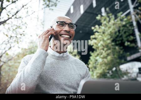 Smiling businessman working on laptop computer sitting outdoors et talking on mobile phone. La gestion des travaux de l'entrepreneur d'affaires assis à l'extérieur. Banque D'Images