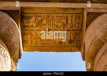 Regardant les hiéroglyphes égyptiens peints colorés en haut de colonnes, salle hypostyle cité parlementaire d'Amon Ra, Temple de Karnak. Louxor, Egypte, Afrique du Sud Banque D'Images