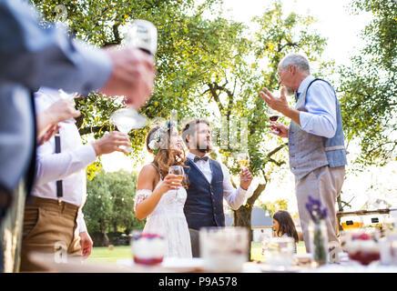 Un homme faisant discours à réception de mariage à l'extérieur à l'arrière-plan. Banque D'Images
