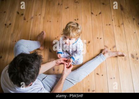Père avec un tout-petit garçon assis sur le sol dans la chambre à la maison. Vue d'en haut. Banque D'Images