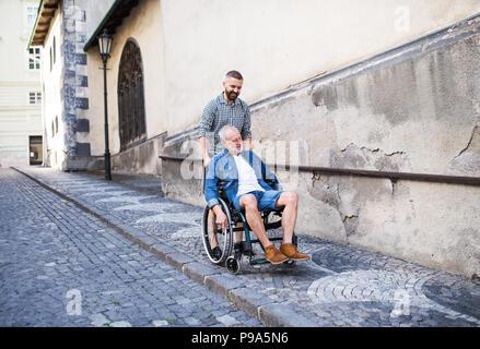 Un fils adulte avec des hauts père en fauteuil roulant, lors d'une promenade en ville. Banque D'Images