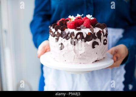 Une femme tient un beau gâteau avec la crème rose framboise fraîche et petits fruits, décoré avec du chocolat. Calories des aliments. Espace libre pour le texte ou une carte postale Banque D'Images