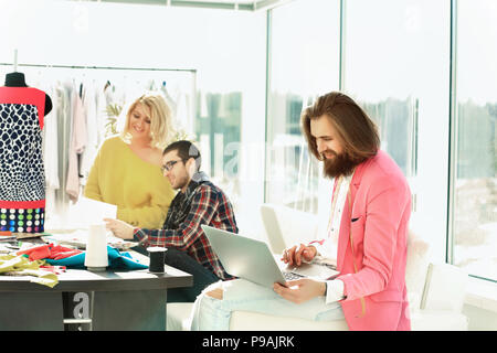 Fashion designer working on a laptop in a creative office Banque D'Images