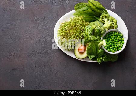 L'alimentation saine manger propre jury source de protéines pour les végétariens: Lucerne, épinards, basilic, petits pois, l'avocat et le brocoli sur fond sombre wi Banque D'Images